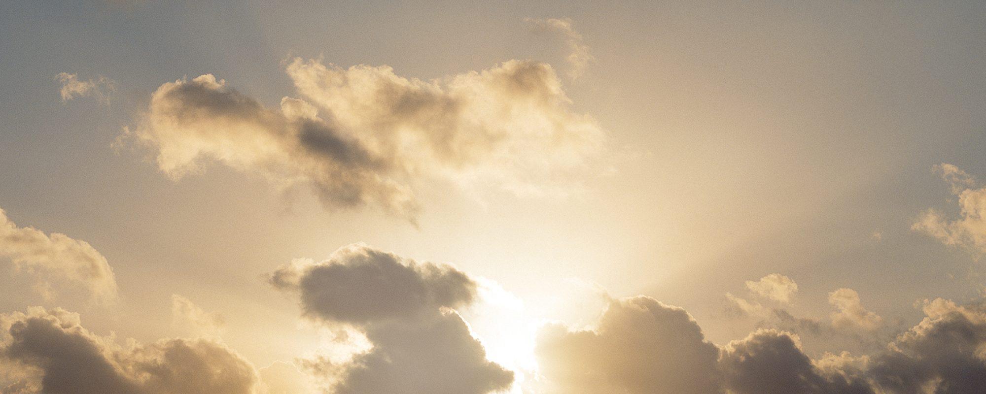 Sonne hinter einzelnen, dunklen Wolken